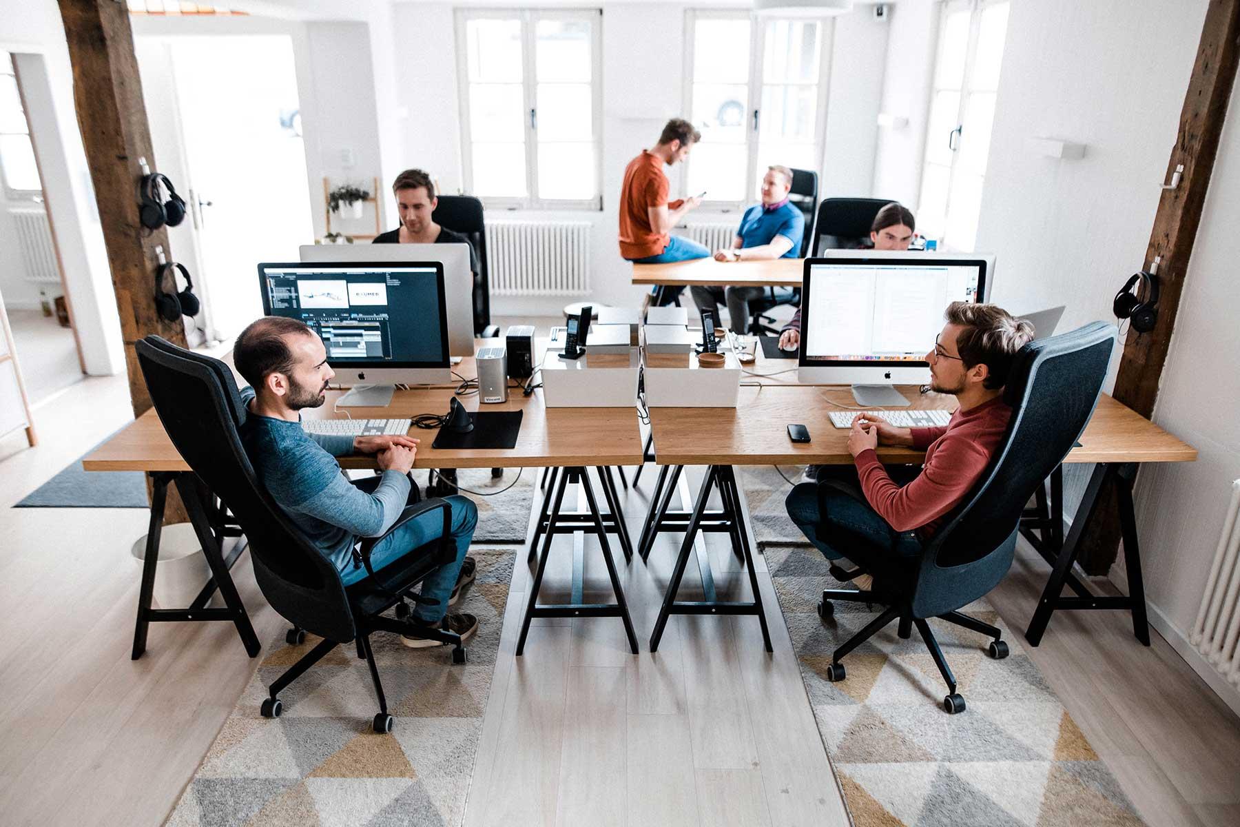 Männer sitzen im Büro und sprechen über Filmproduktion in Dortmund