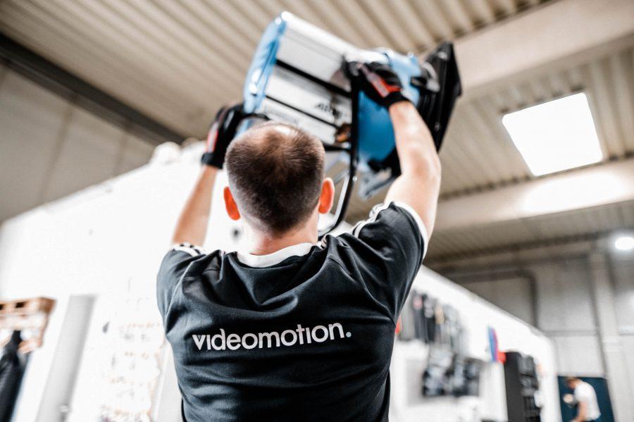 Bild zeigt Mann der Filmlampe aufbaut, die zu den Kosten eines Imagefilms beiträgt