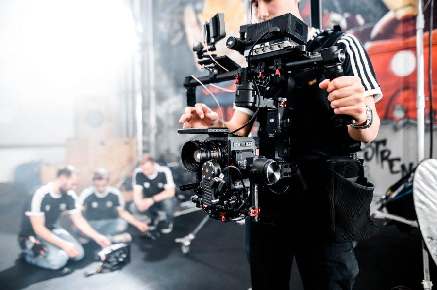 Bild zeigt Kameramann, der Filmkamera in der Hand hält, welche zu den Kosten eines Imagefilms beiträgt.
